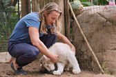 Young man makes friends with white lioness cub — Stock Photo
