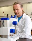 Mikroskop laboratuar önlüğünü erkek araştırmacı görünüyor — Stok fotoğraf
