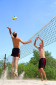 Two men playing beach volleyball - short balding man wins over t — Stock Photo