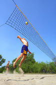 Playing beach volleyball - fat man jumps high to spike the ball — Stock Photo
