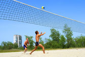 Two men playing beach volleyball — 图库照片
