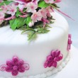 White cream cake with pink flowers and green leaves — Stock Photo