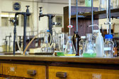Glassware on wooden tables in chemical lab — Stock Photo