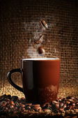 Brown cup of coffee with coffee beans — Stock Photo