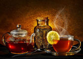 Glass teapot and cup on golden background — Stock Photo