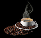 Cup of coffee with grains on a black background — Stock Photo