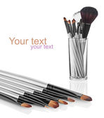 Makeup brush set in a glass beaker isolated on white background — Stock Photo