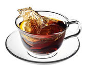 Hot tea splashes as a lemon slice or sugar cube is dropped into — Stock Photo