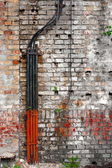 Abandoned brick wall with cables — Stock Photo