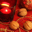 Christmas table decoration with chains, candle and walnuts — Stock Photo