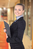 Cheerful beautiful business woman with clipboard writing, — Stock Photo