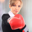 Portrait of young female entrepreneur wearing boxing gloves — Stock Photo