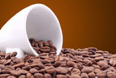 Small white cup of coffee grains — Stock Photo