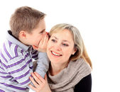 A young boy is whispering a secret in his mothers ear — Stockfoto