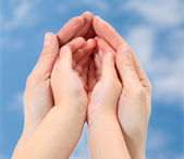 Hands of mother and baby close-up on the sky — Stock Photo