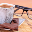 Foto Stock: Cup of coffee with chocolate and glasses