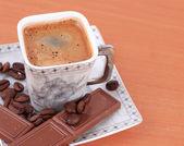 テーブルの上にチョコレートとコーヒーのカップ — ストック写真
