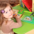 Foto Stock: Beautiful little girl reading fairy tales at table