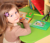 Beautiful little girl reading fairy tales at the table — Stockfoto
