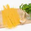 Royalty-Free Stock Photo: Spaghetti on a wood board with wood spoon