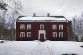 Nieve y grande casa de madera roja — Foto de Stock