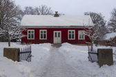 Small wooden red house covered by snow — Stock Photo