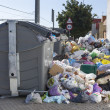 Bags full of trash surrounding dumpsters - Stock Photo