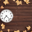 Stock Photo: Clock and leaves on a brown plank