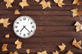 Clock and leaves on a brown plank — Stock Photo