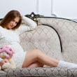 Young pregnant woman sitting on the sofa — Stock Photo