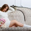 Young pregnant woman sitting on the sofa - Stock Photo