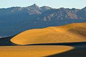 Geschwungene sanddünen unter berg — Stockfoto