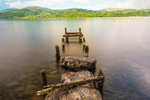 Calm lake with ruined piers — Stock Photo