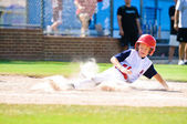 Little league baseball player sliding home. — 图库照片