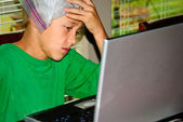 Boy on laptop stressed with headache — Stock Photo