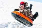 αγόρι επάνω στον αέρα σε ένα σωλήνα στο χιόνι — Φωτογραφία Αρχείου