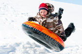 Boy up in the air on a tube in the snow — Fotografia Stock