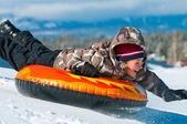Gelukkige jongen rijden een buis in sneeuw — Stockfoto