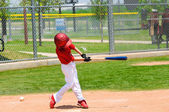 Young baseball player swinging bat — Stock Photo