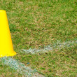 Yellow cone on grass field — Stock Photo