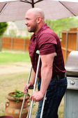 Man on crutches — Stock Photo