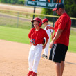 Baseball player and baseball coach at first base. - Stock Photo