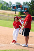 Baseball player and baseball coach at first base. — Stock Photo