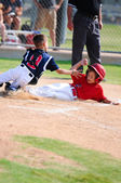 Little league speler glijden home. — Stockfoto
