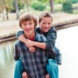 Two young boys piggy back — Stockfoto