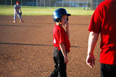 Baseball boy looking at coach — Stock Photo