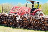 Stack of firewood and tractor — Stock Photo