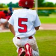 Kneeling baseball boy for injured player — Stock Photo