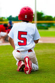 Kneeling baseball boy for injured player — Stock Photo