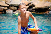 Boy getting out of swimming pool — Stock Photo